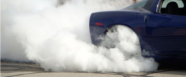 A Corvette produces a plume of smoke from its rear tires.