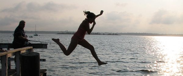 A silhouetted girl jumps off a pier