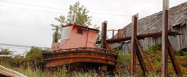 A rusty boat sits adjacent to a weathered wooden structure